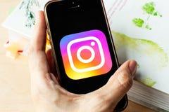 Mano che tiene uno smartphone con un'icona di Instagram sullo schermo immagine stock libera da diritti