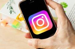 Mano che tiene uno smartphone con un'icona di Instagram sullo schermo fotografie stock libere da diritti