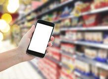 Mano che tiene uno smartphone moderno in supermercato Fotografie Stock