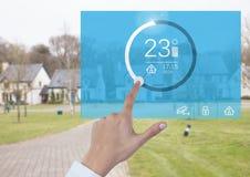 Mano che tocca un'interfaccia di App di temperatura del sistema di automazione domestica Fotografia Stock