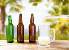 Mano che versa birra leggera in una tazza, bottiglie sulla tavola di legno immagini stock