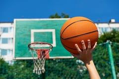 Mano con baloncesto en el fondo del aro de la cesta del escudo Fotos de archivo libres de regalías