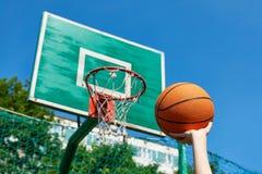 Mano con baloncesto en el fondo del aro de la cesta del escudo Fotografía de archivo