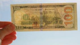 Mano con cientos billetes de banco del dólar Imagenes de archivo