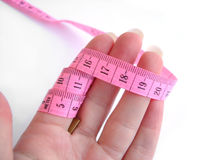 Mano con cinta métrica rosada contra el fondo blanco Imagen de archivo libre de regalías