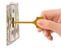 Mano con clave y el dinero Imágenes de archivo libres de regalías
