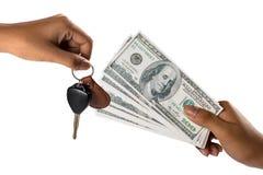 Mano con claves del dinero y del coche Imagen de archivo