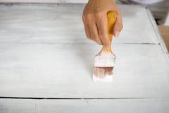 Mano con de madera blanco de la pintura del cepillo fotos de archivo libres de regalías