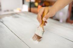 Mano con de madera blanco de la pintura del cepillo imágenes de archivo libres de regalías
