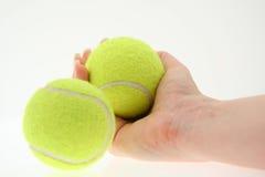 Mano con due sfere di tennis Immagini Stock Libere da Diritti