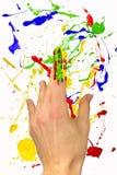 Mano con el índice pintado en fondo Imagen de archivo