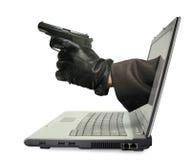 Mano con el arma en monitor de la computadora portátil Fotos de archivo