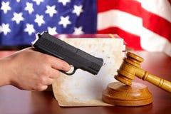 Mano con el arma y el mazo de los jueces Fotografía de archivo libre de regalías