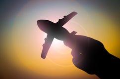 Mano con el avión de papel en la trayectoria del sol Imágenes de archivo libres de regalías