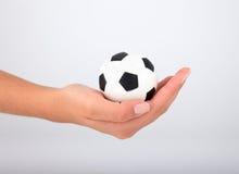 Mano con el balón de fútbol Imagen de archivo libre de regalías