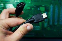 Mano con el cable de HDMI imagen de archivo