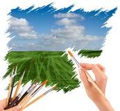 Mano con el cepillo del panit que pinta un paisaje hermoso del verano foto de archivo libre de regalías
