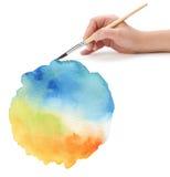 Mano con el cepillo y el fondo pintado color Imágenes de archivo libres de regalías