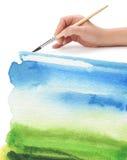 Mano con el cepillo y el fondo pintado color Fotos de archivo