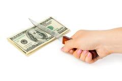 Mano con el dinero del corte del cuchillo fotografía de archivo libre de regalías