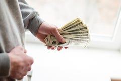 Mano con el dinero unas centenas euros en billetes de banco Aproveche las manos Beneficios, ahorros fotografía de archivo libre de regalías