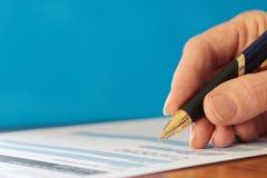 Mano con el fondo de firma del azul del primer de la forma de la pluma Imágenes de archivo libres de regalías