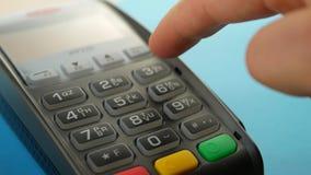 Mano con el golpe fuerte de la tarjeta de crédito con el terminal para la venta y pagar orden almacen de metraje de vídeo