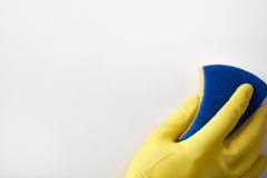 Mano con el guante amarillo con el fondo del estropajo Imagen de archivo libre de regalías