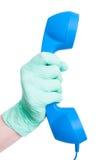 Mano con el guante médico que sostiene un receptor de teléfono del vintage Imagen de archivo
