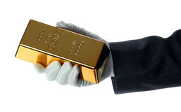 Mano con el guante que sostiene un lingote de oro fotos de archivo libres de regalías