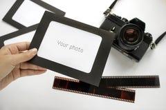 Mano con el marco de la foto en fondo y la película de la cámara Fotografía de archivo libre de regalías