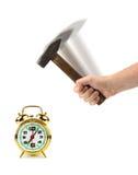 Mano con el martillo y el reloj de alarma Fotos de archivo libres de regalías