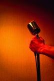 Mano con el micrófono retro Imagenes de archivo