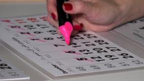 Mano con el movimiento rosado del marcador los días pasados de mes de diciembre del calendario de 2016 años metrajes
