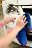 Mano con el paño de la microfibra que limpia un coche con la cera del espray Fotos de archivo libres de regalías