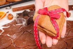 Mano con el pan de jengibre o las galletas por tiempo de la Navidad y los accesorios frescos para cocer Fotos de archivo libres de regalías
