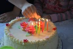 Mano con el partido que enciende la vela en la torta Imágenes de archivo libres de regalías