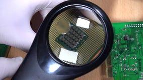 Mano con el procesador de examen de la CPU del ordenador de la lupa almacen de metraje de vídeo