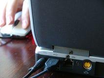 Mano con el ratón y una computadora portátil Fotos de archivo libres de regalías