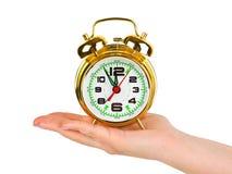 Mano con el reloj de alarma Foto de archivo libre de regalías
