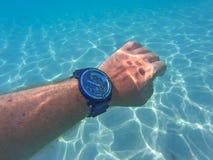 Mano con el reloj debajo del mar imagen de archivo