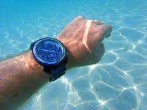 Mano con el reloj debajo del mar fotografía de archivo libre de regalías