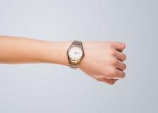 Mano con el reloj que muestra tiempo exacto Imagen de archivo libre de regalías