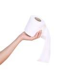 Mano con el rollo del papel higiénico Imagen de archivo