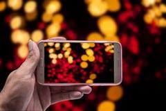 Mano con el smartphone y la luz borrosos, trayectoria de recortes Fotografía de archivo