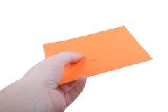 Mano con el sobre anaranjado imagen de archivo
