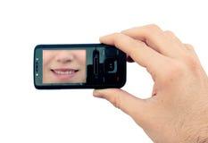 Mano con el teléfono móvil y la sonrisa Foto de archivo libre de regalías