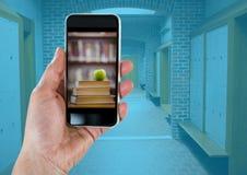 Mano con el teléfono que muestra la pila del libro con la manzana verde contra vestíbulo con la capa azul Fotografía de archivo