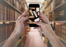 Mano con el teléfono que muestra los libros derechos contra los estantes borrosos Imagenes de archivo