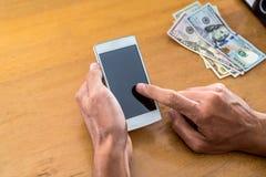 mano con el teléfono y los dólares Fotografía de archivo libre de regalías